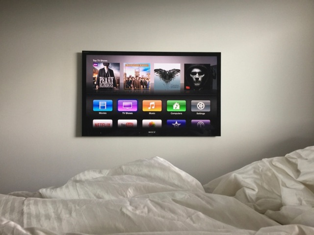 A wall mounted flat screen TV with Apple TV