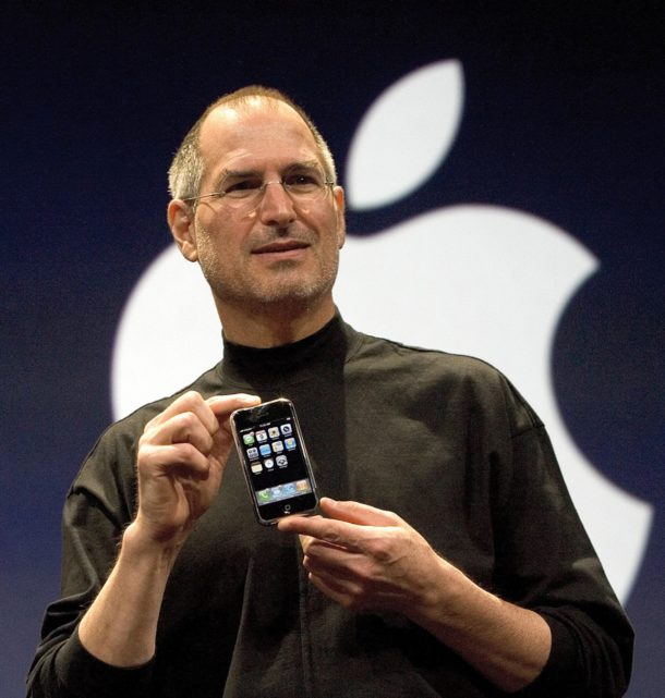 Steve Jobs holding the first ever iPhone